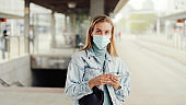 Young blonde woman wearing mask waiting in a bus station and using phone.