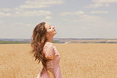 Beautiful happy free young woman fashion enjoying nature peace, looking up to the sky isolated wheat field background