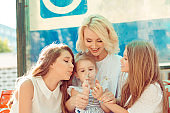 Happy family mother and three girls blowing on a dandelion flower