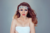 Sexy and beautiful. Beauty Queen bride woman with bright blue crystals jewelry on head looking at you camera purple bridal makeup isolated light gray white background wall