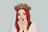 Shocked beauty queen beautiful woman with big eyes, with open month, with hand on cheeks looking at you camera. Pretty woman with crystal crown on head isolated on light green gray background