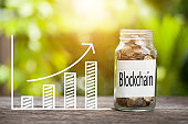 Blockchain Word With Coin In Glass Jar and graph up. Business Concept