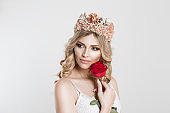 Beauty Queen bride with bright pink crown holding a red rose near her cheek looking side wards, light bridal makeup isolated grey white background wall