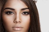 Trendy style makeup. Closeup portrait cropped image brunette woman face with beautiful shiny eye makeup lips on white grey background wall. Dark skin beauty queen thick eye brows brown hair contouring