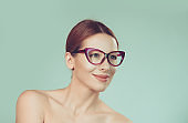 woman looking up to the side wearing eyeglasses isolated on light green white wall background