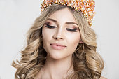 Beautiful blonde girl in a golden crown on grey background, eyes closed