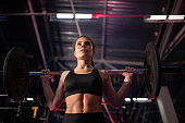 Determined sportswoman with barbell in gym