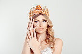 Beauty crowned queen girl woman actress miss bride hands on face showing manicure gel art nails looking at you camera isolated on white. Full makeup diamond golden pink crystals crown pastel colors