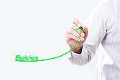 Businessman hand writing growth graph for blockchain.