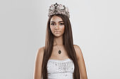Dark beauty. Closeup portrait african american indian mixed race woman slightly smiling looking at you camera on white grey background. Crowned beauty queen miss contestant bride to be fashion model