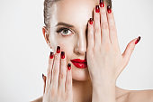 Sexy Beauty Girl with false eyelashes Black Red gradient Lips, Nails. Provocative natural Make up. Luxury Woman looking at you camera hands on face Fashion Brunette Portrait isolated white background