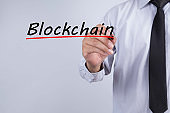 Businessman hand writing blockchain with red marker on transparent wipe board, business concept.