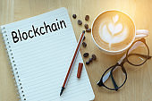 Concept blockchain  message on notebook with glasses, pencil and coffee cup on wooden table.