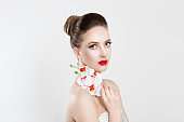 Beautiful Girl With  holding white orchid Flowers isolated light grey white background. Beauty Model Woman Face smiling with red lips and nails. Perfect Skin. Professional Make-up. Makeup. Fashion Art