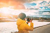 Aurlandsfjellet, Norway. Young Happy Woman Tourist Traveler Photographer Taking Pictures Photos Of Aurlandsfjellet Scenic Route Road. Norwegian Landmark And Popular Destination