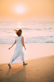 Goa, India. Young Caucasian Woman With Fluttering Hair In Wind In White Dress Walking Along Seashore In Sunrise Sunset Time