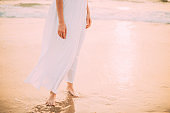 Goa, India. Close Legs And Hands Of Young Woman In White Dress Near Sea Ocean In Sunny Time