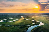 Aerial View. Beautiful Sunset Sun Sunshine Above Green Forest, Meadow And River Landscape In Sunny Evening. Top View Of European Nature From High Attitude In Summer Sunrise. Bird's Eye View. Belarus