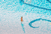 Adult Caucasian Lady Woman Standing In Hotel Swimming Pool In Sunny Summer Day. Vacation In Hotel