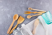 Zero waste concept. Cotton bag, glass and wooden cutlery on gray background. Set of eco friendly wooden cutlery and mason jar. Plastic free concept. Minimalism. Top view. Copy space