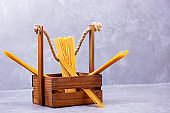 Pasta in a wooden box. Donation wooden box with raw spaghetti on a gray background. Social assistance with food. Safe food delivery. Food donation concept. Copy space