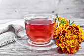 Tea herbal of marigolds in glass cup on wooden board