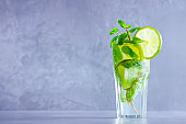 Mojito cocktail with lime and mint in tall glass. Fresh mojito in glass on a gray background