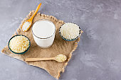 Rice milk and rice seeds on a gray background. Rice milk in glass on sackcloth. Vegan non-dairy milk on cement background. Alternative milk from rise. Rustic style. Copy space