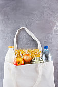 Food donations in linen bag. Food delivery in eco bag. Eco bag with food supplies food stock. Top view. Copy space