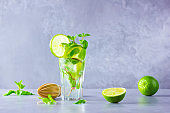 Mojito cocktail with lime and mint in tall glass. Fresh mojito in glass on a gray background. Refreshing mint cocktail with lime. Copy space