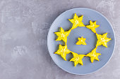 Carambola on a gray plate. Sliced fresh carambola on a gray background. Slices of star fruit. Trendy food. Copy space