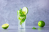 Mojito cocktail with lime and mint in tall glass. Fresh mojito in glass on a gray background. Refreshing mint cocktail with lime. Infused water