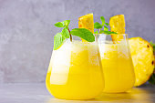 Pineapple cocktail in two glasses on a gray background. Cold pineapple cocktail with mint. Summer tropical cocktail. Healthy drink