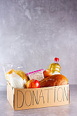 Donation box with food. Open cardboard box with oil, milk, canned food, pasta and bread. Grocery set on gray background. Donation concept