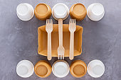 Zero waste. Disposable tableware. Eco-friendly disposable utensils made of bamboo wood and paper on a gray background. Paper cups, fast food containers and bamboo wooden cutlery