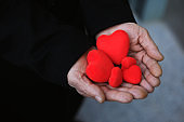 Senior hand holding red hearts