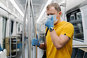 Horizontal shot of man passenger coughs and has problems with breathing, wears disposable mask and gloves, stands in public transport, metro, prevents from coronavirus. Public health solution