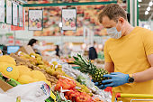 Horizontal shot of man selects pineapple in store wears medical mask and gloves buys fresh fruit during coronavirus outbreak or virus pandemic poses in grocery department. Protection, prevent measures