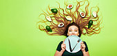 beautiful girl lying with avocado fruits on long hair, young woman hold plate with cutlery knife and fork, concept health and dieting