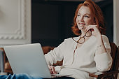 Horizontal shot of thoughtful young redhead woman concentrated somewhere, works on freelance project, holds spectacles, keeps laptop computer on knees, enjoys online job, creats new publication