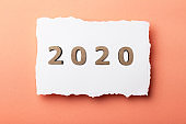 background with wooden figures of the date 2020 on white paper, new year concept, calendar cover design, new colored page