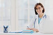 Professional woman doctor writes down notes, poses at desktop in office with laptop, wears white coat, spectacles and phonendoscope around neck, looks through medical documents. Healthcare concept