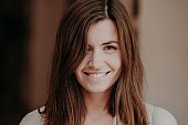 Close up portrait of happy brunette woman with toothy smile, looks happily at camera, healthy skin, natural beauty, poses indoor. Cheerful young girlfriend feels glad. Positive emotions concept