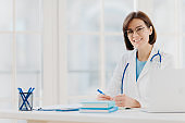 Medical specialist wears white gown with stethoscope, works in hospital, makes notes, poses at own cabinet, sits at table with laptop computer in office smiles happily. Health care and medical concept