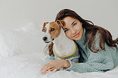 Image of lovely brunette lady leans at pedigree jack russel terrier, embraces pet with love, spend time together, lie on white bedclothes. People, animals, love and friendship concept. Dog lover