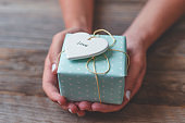 Woman holding a gift box with a heart shape with love and a bow of string on top.