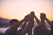 Group of people holding hands in celebration and friendship.