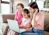 Happy grandmother with little kid and daughter having fun online with laptop at home