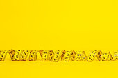 Measuring tape on a yellow background. Measuring tape in the shape of a spiral twisted on a yellow background. Slimming and diet concept, copy space