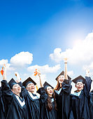 happy  students in graduation gowns holding diplomas on cloud background
